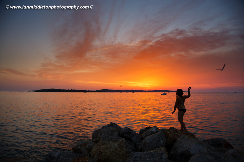 Girl throwing stones in the sea as the sun sets over the Brijuni Islands, Croatia. Seen from Puntižela Beach, Štinjan north of Pula.