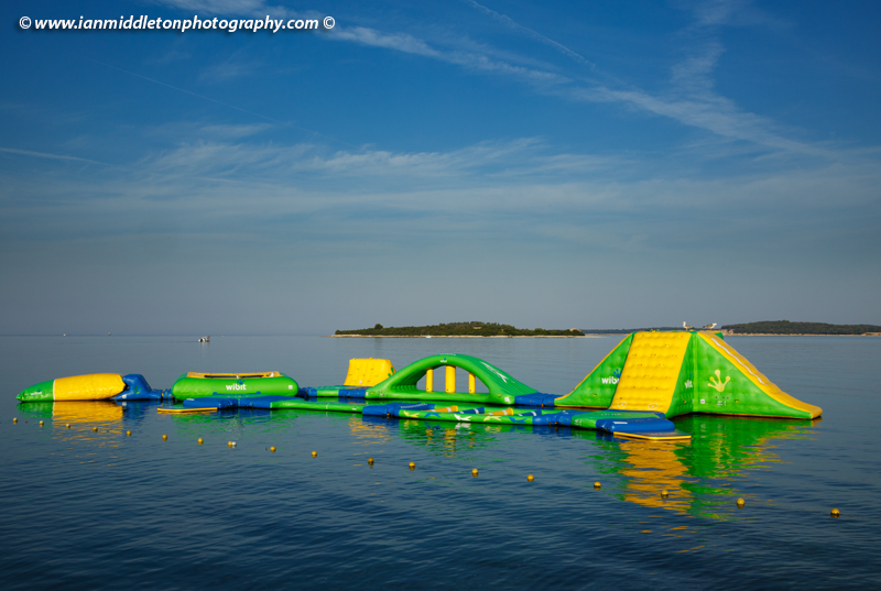 Morning at Puntižela Beach, Štinjan north of Pula. View of the Brijuni Islands and the childrens inflatable playground on the water.