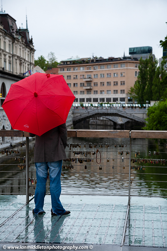 Man holding a red umbrella and standing on The Butchers' Bridge looking over the Ljubljanica river towards the Trznica (market) Triple Bridge on a rainy day in Ljubljana, Slovenia. The wire fence on the bridge is covered with padlocks put there by locals and tourists. All this region was designed by Slovenia's most celebrated architect, Joze Plecnik.