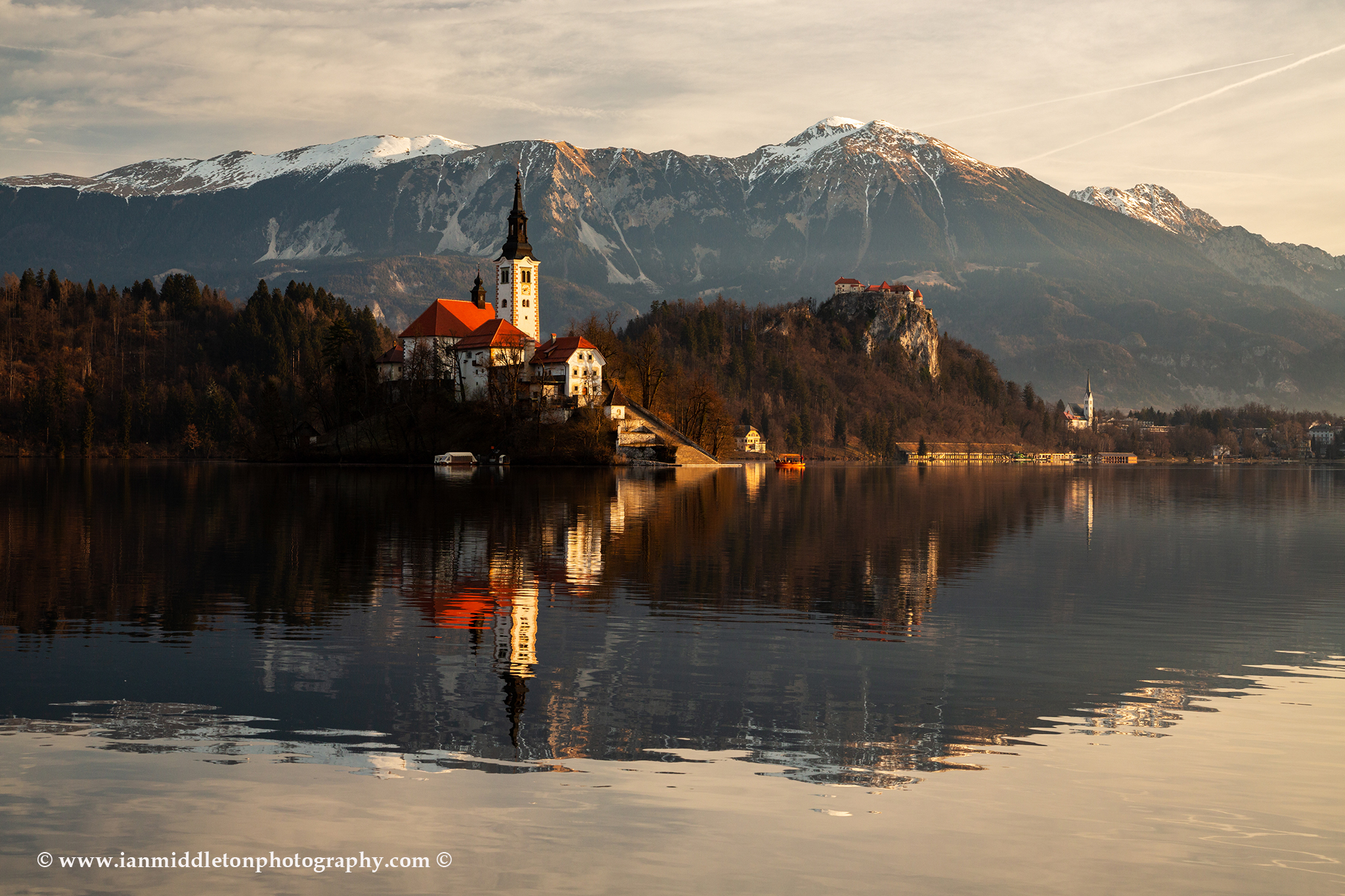 Morning at Lake Bled and the island church of the assumption of Mary with the Karavanke mountains in the background, Slovenia.