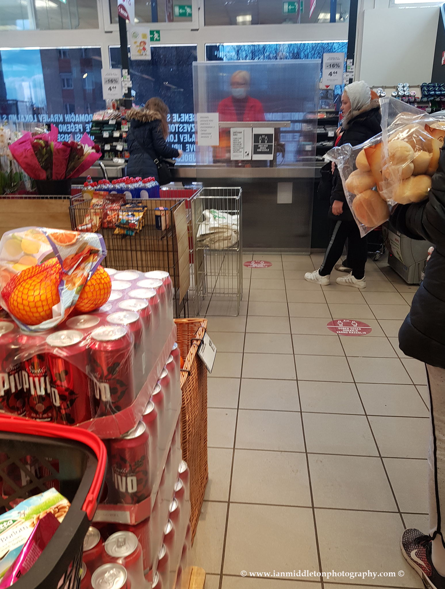 Queuing at the till in Mercator with the cashier behind a screen and wearing a mask. This is in a suburb of Ljubljana, Slovenia. Mercator is Slovenia's largest supermarket chain. Taken 23-3-2020